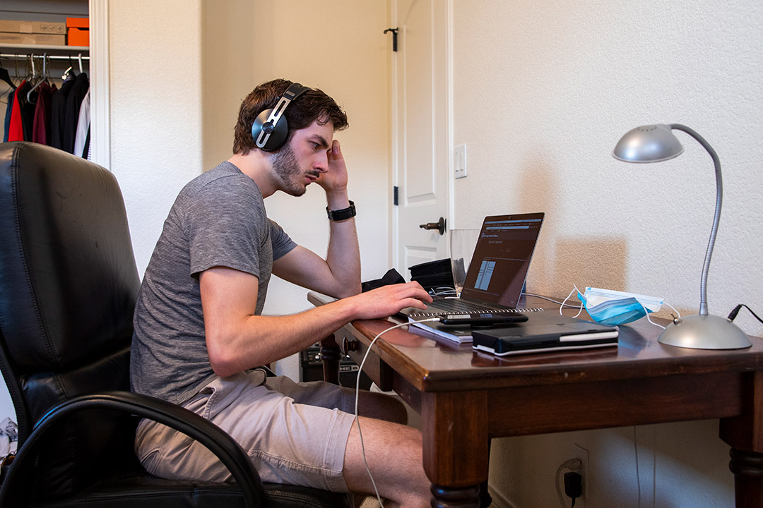 student sitting at desk at home wearing headphones and working on laptop.