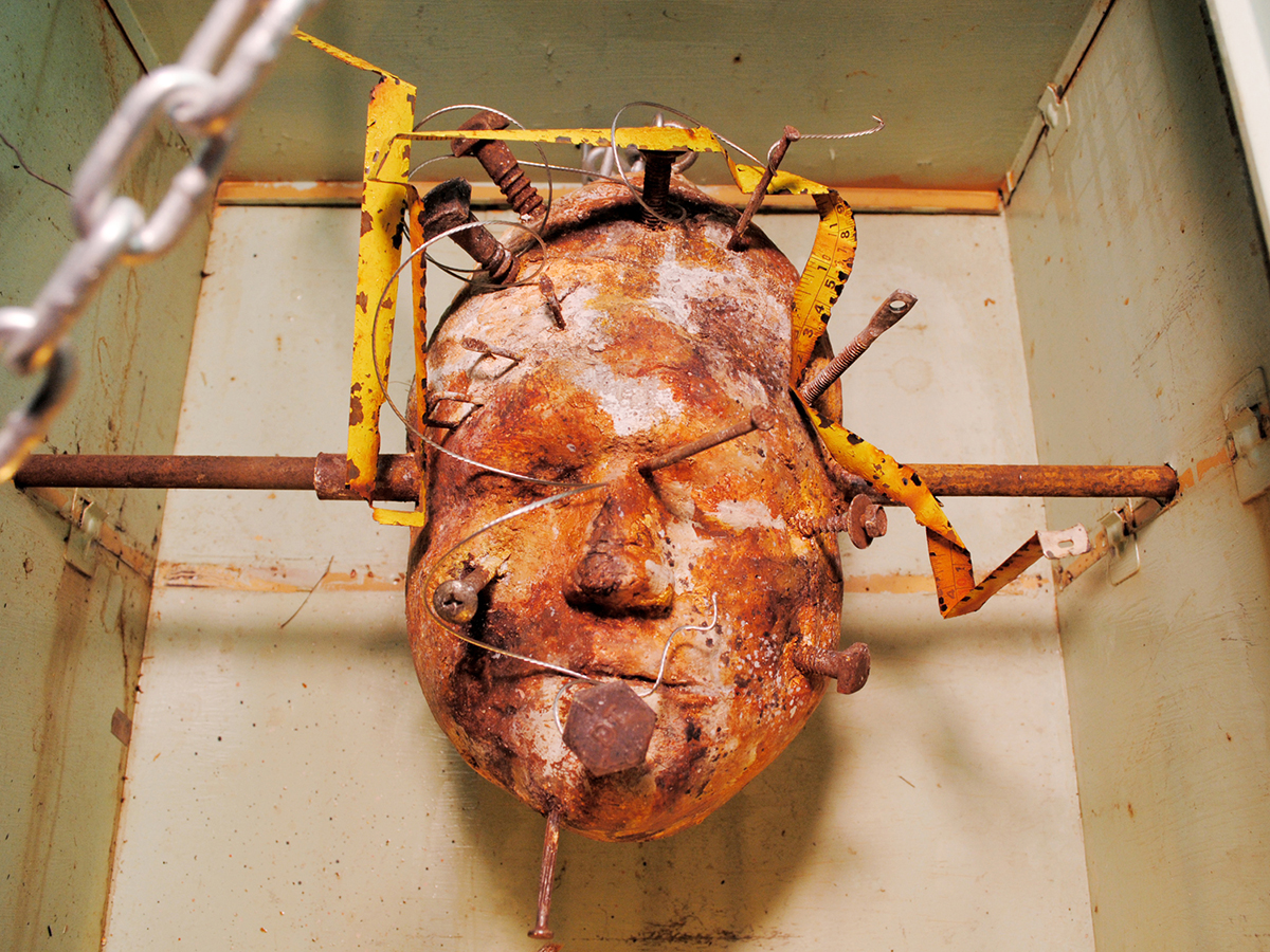 A found object sculpture of a head with rusty nails and bars going through it.