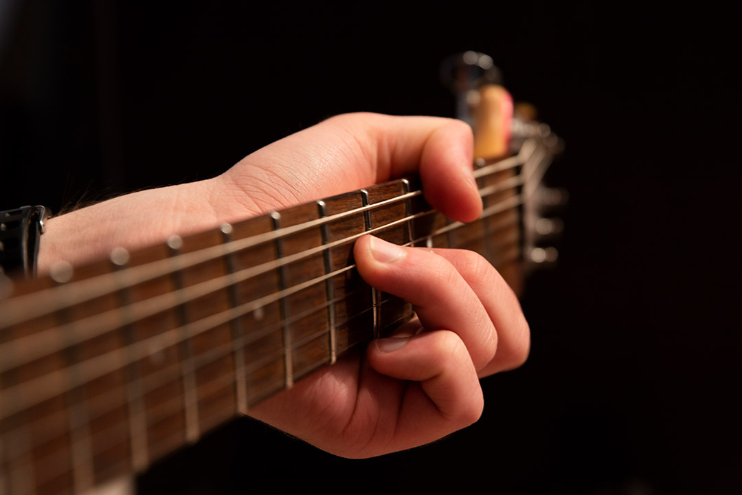 closeup of hand on fretboard of a guitar.