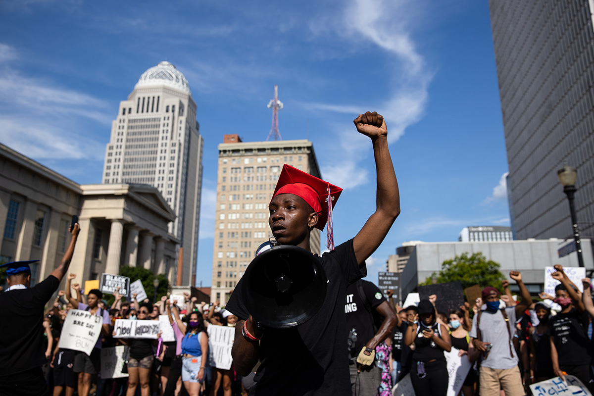 A boy wearing a graduating cap raises his left arm in the air, surrounded by a crowd of fellow protestors.