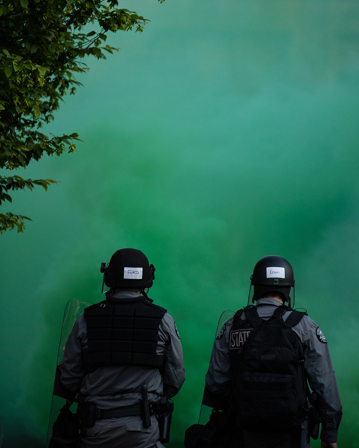 Two police officers stand behind a green-colored gas.