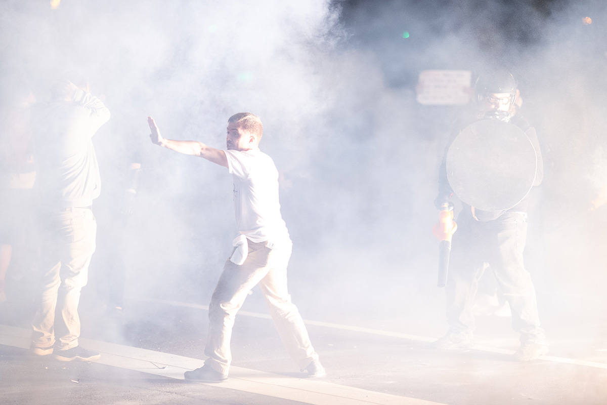 A man, surrounded by a white fog, motions to a crowd of fellow protestors.