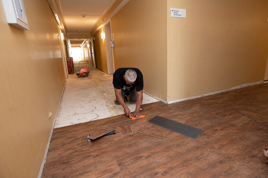 person installing vinyl flooring that looks like hardwood in a former hotel.