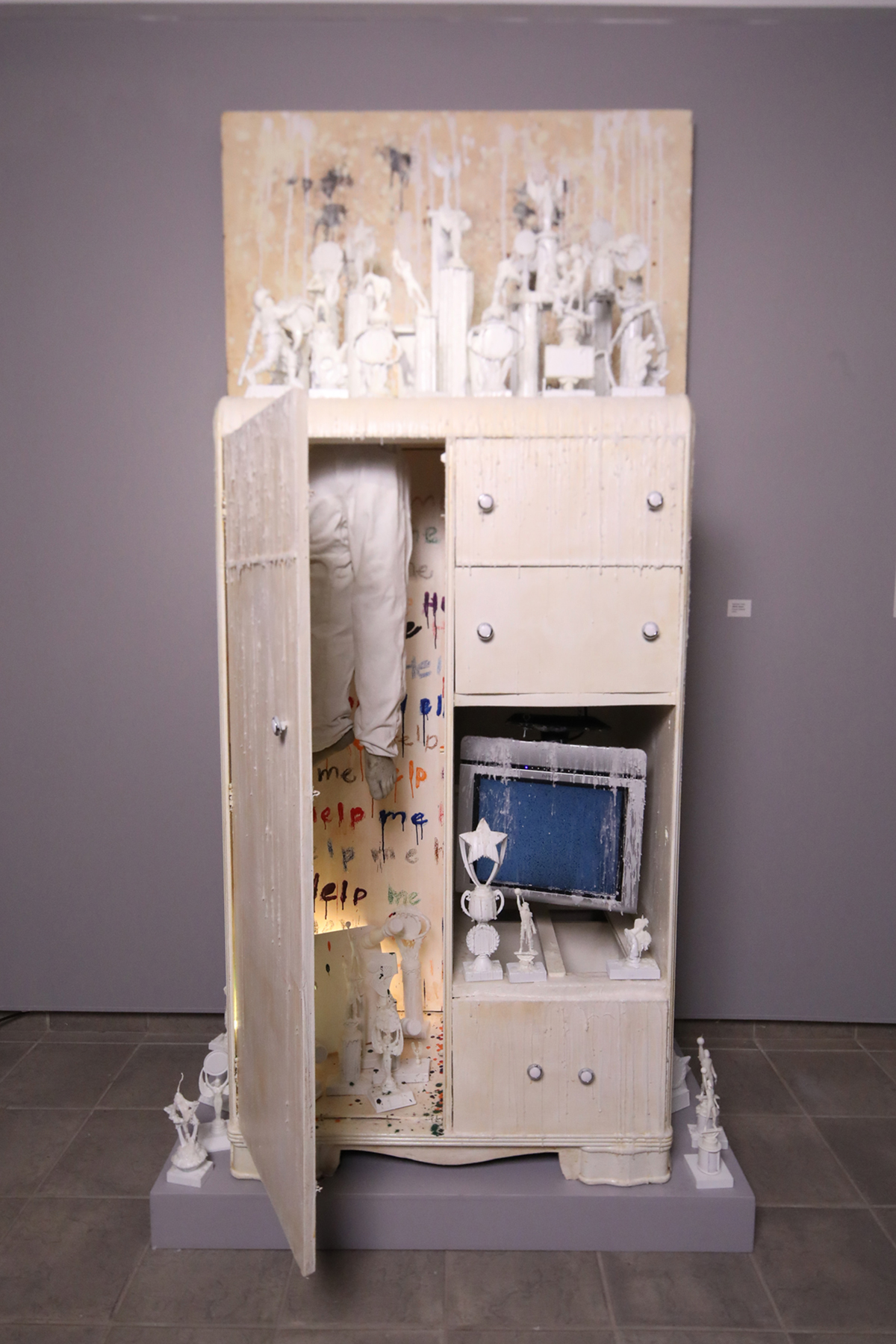 A found object sculpture featuring a dresser, small white sculptures and other objects.