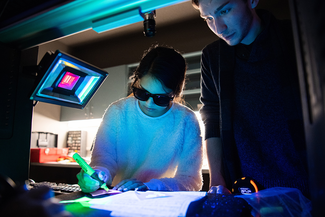 student wearing sunglasses looking at document under black lights.