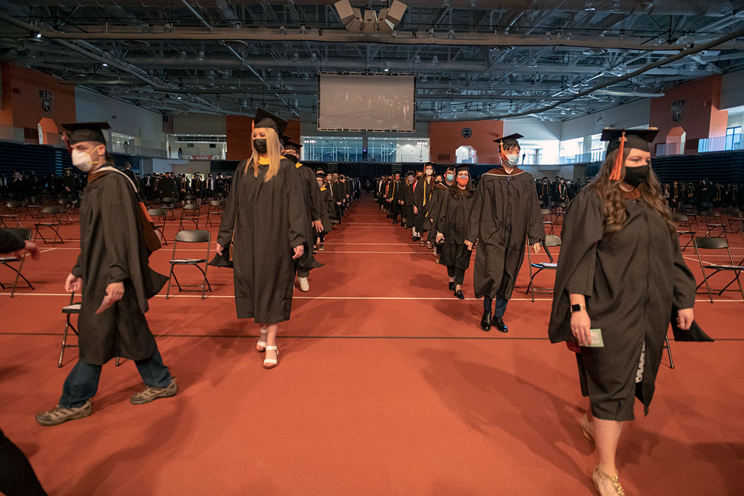 Students wearing graduation regalia processing up an aisle in two lines.
