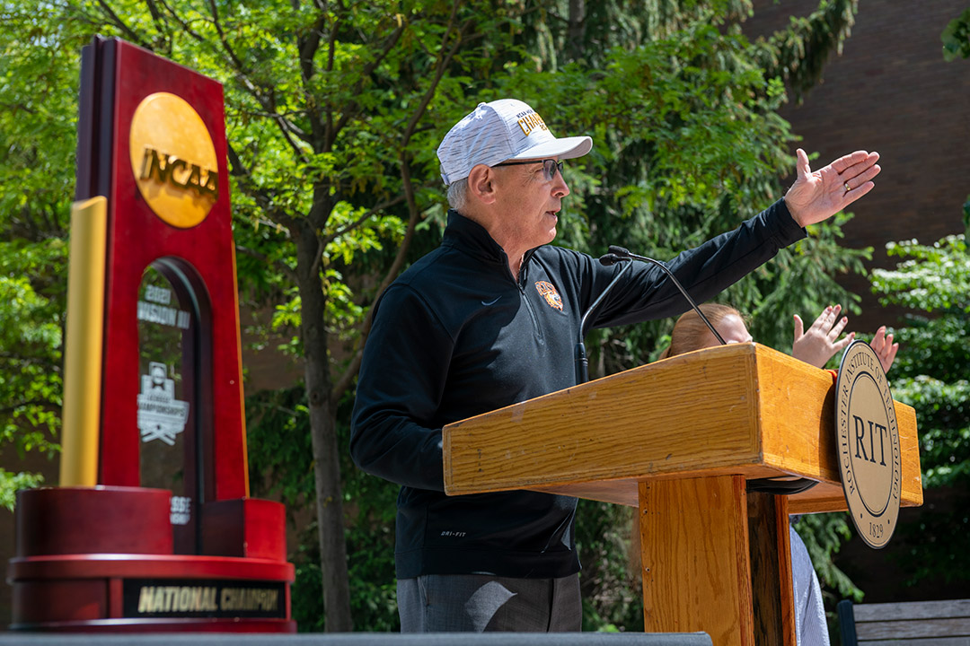 athletics director speaking outdoors at a podium.
