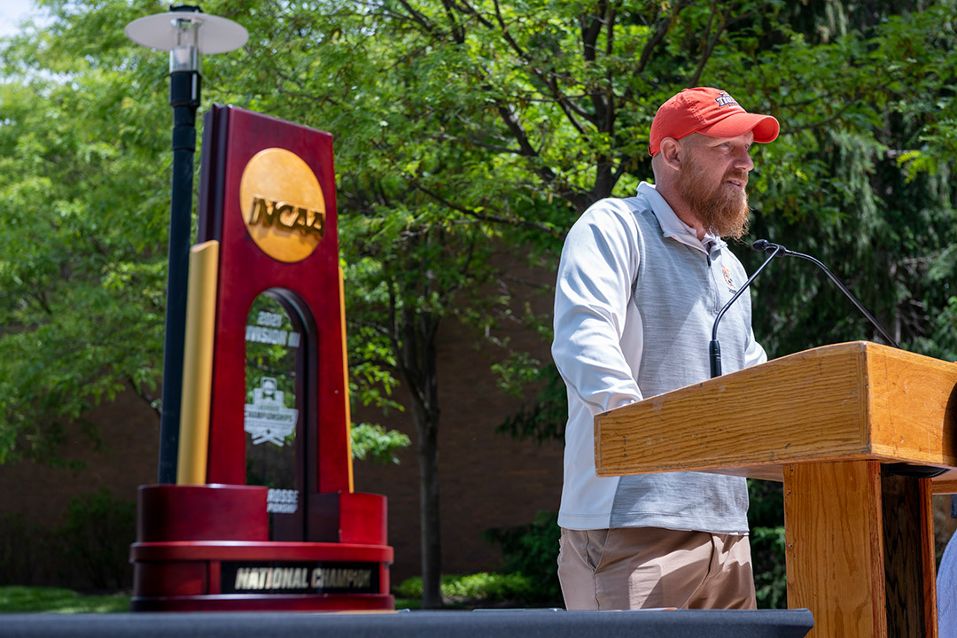 coach speaking outdoors at a podium.