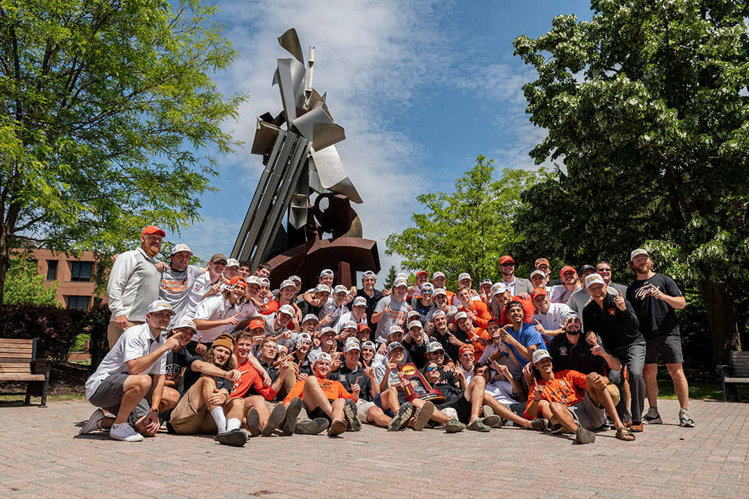 men's lacrosse team gathers in front of the Sentinel statue.