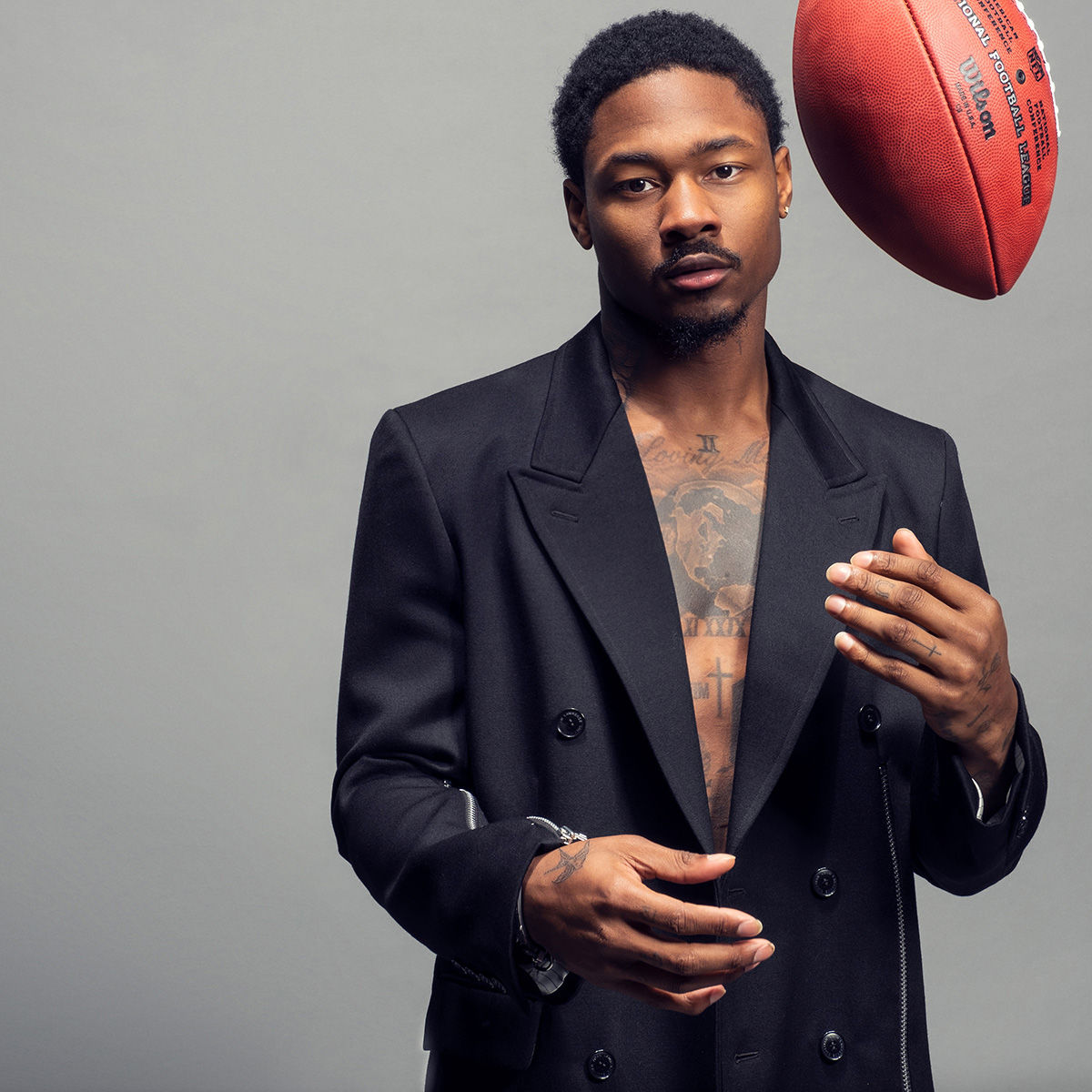 Stefon Diggs, donning a blazer, flips a football in the air.