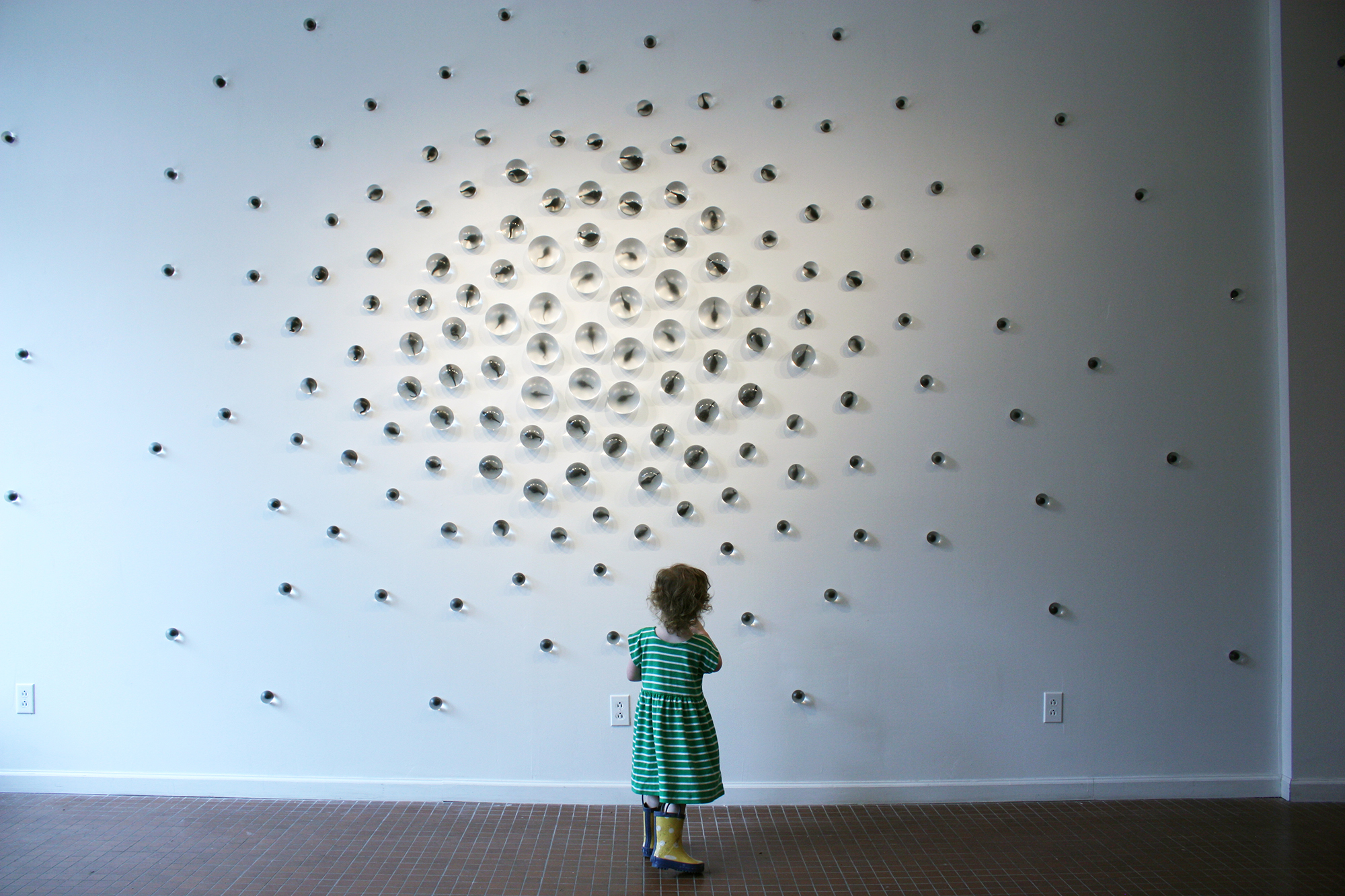 Toddler stands in front of a large art piece on a wall