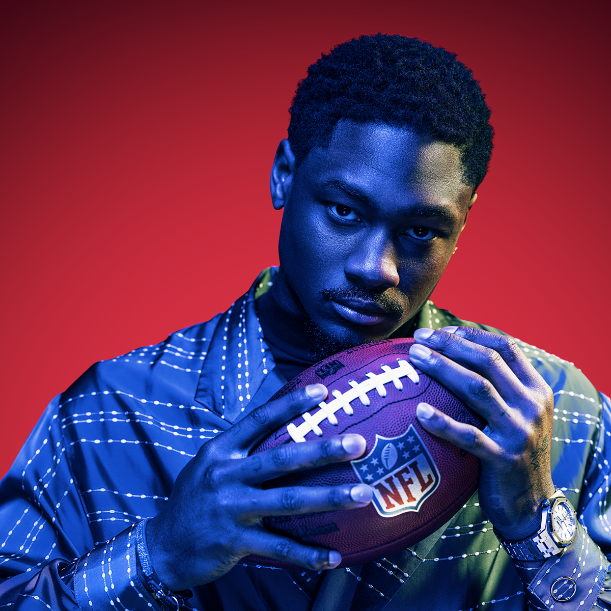 Stefon Diggs holding a football against a red background.