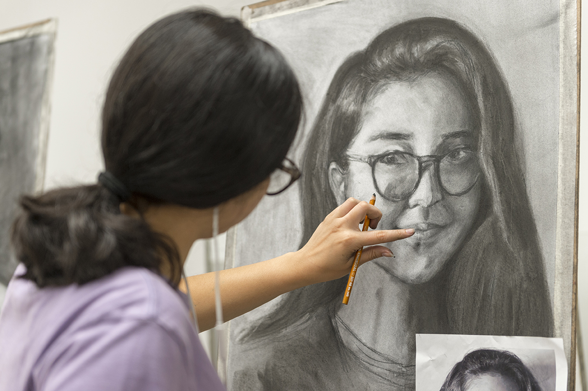A student working on the self-portrait assignment