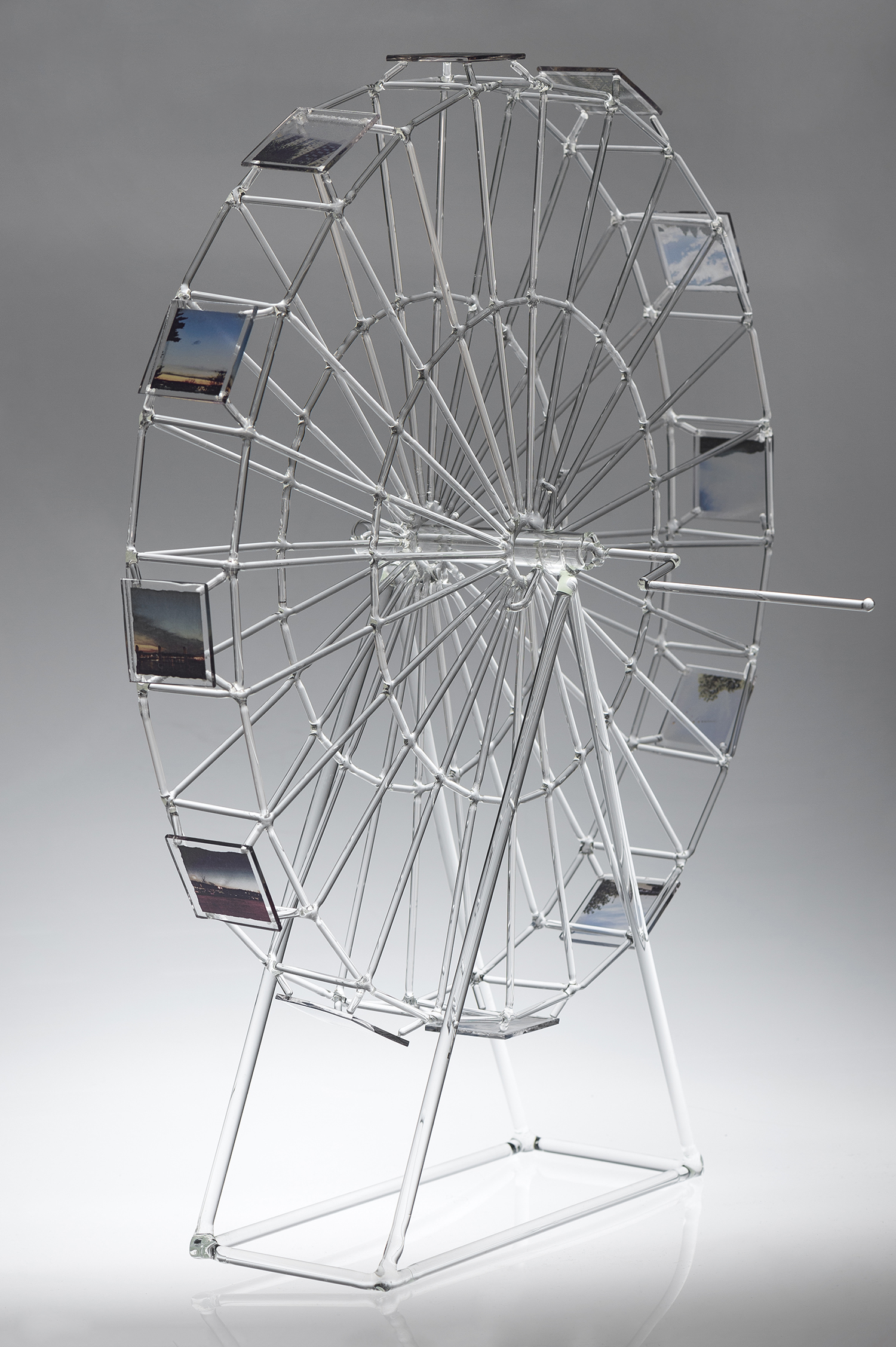 small glass ferris wheel with images on the outside