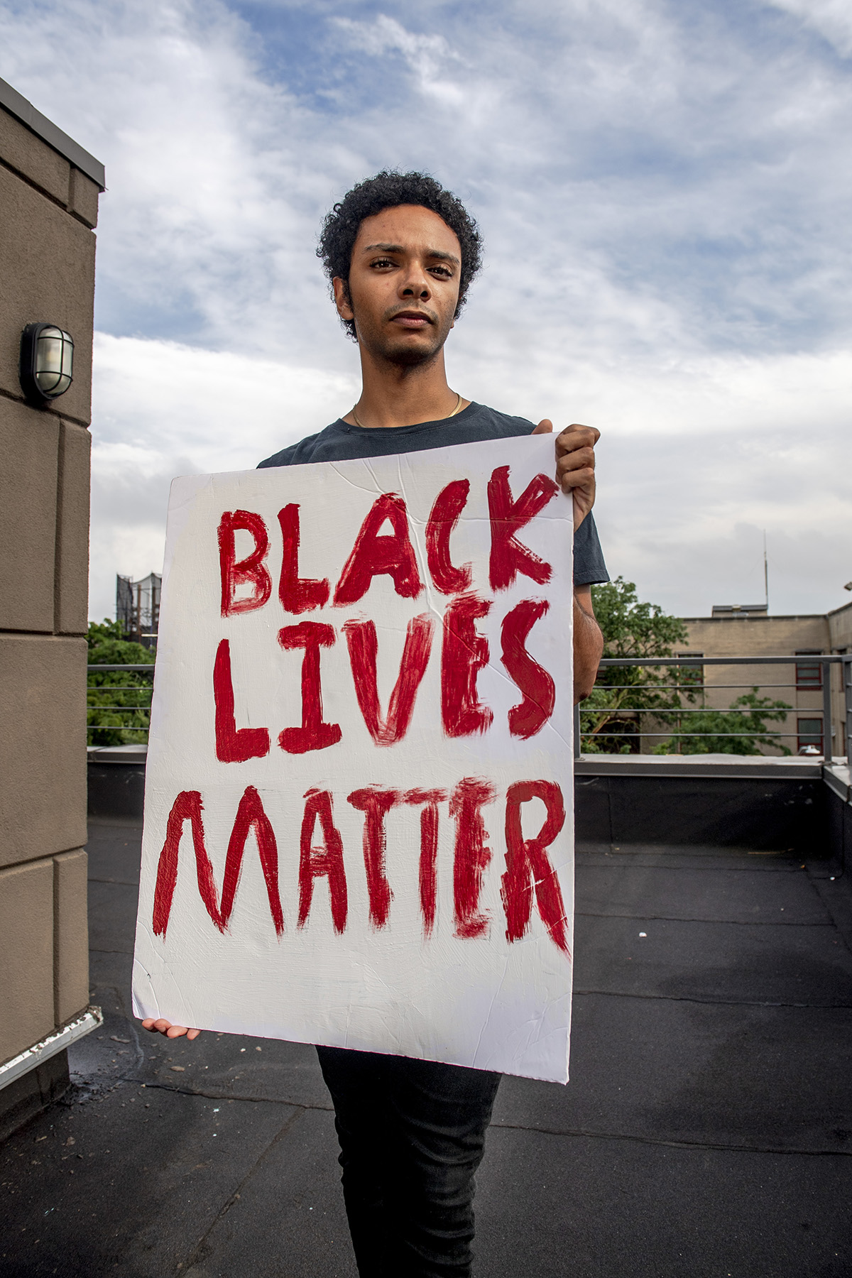 a boy holds a sign that reads Black Lives Matter in red.
