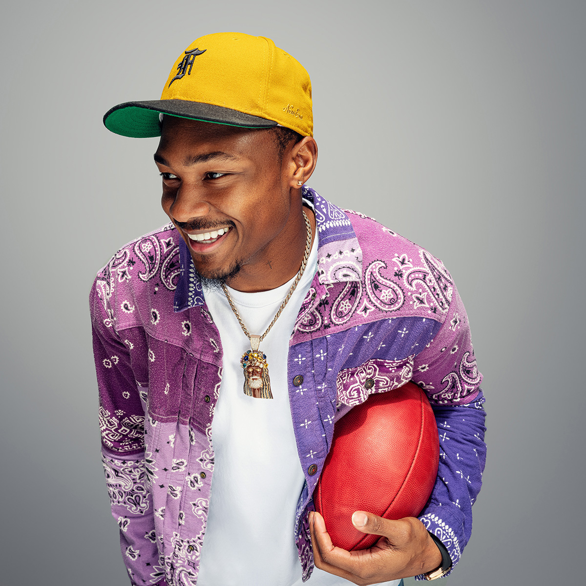 Stefon Diggs holding a football and smiling.