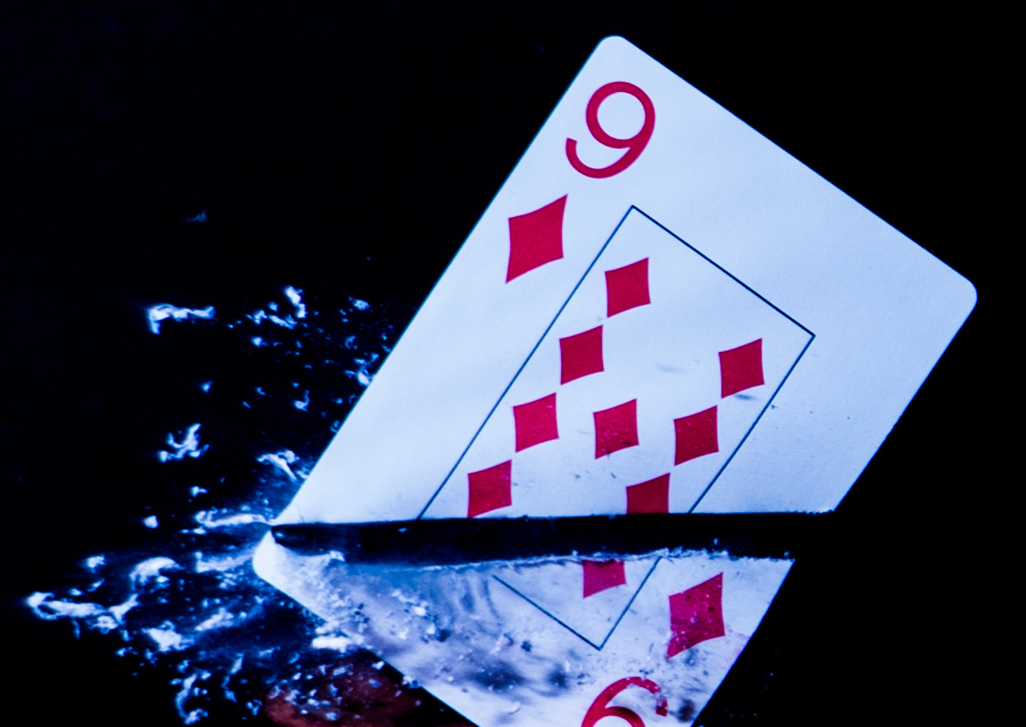 A photo of a bullet going through a playing card.