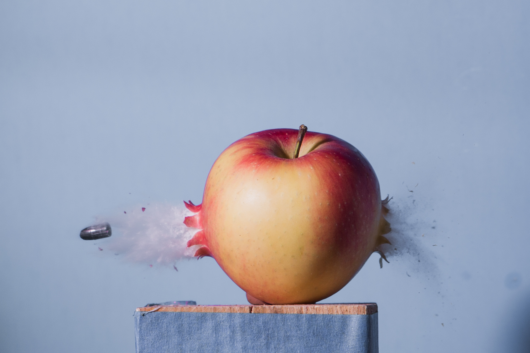 A photo of a bullet going through an apple.