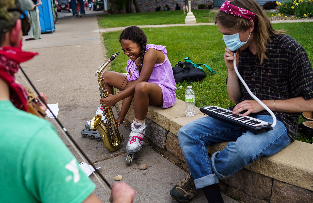 A girl plays the saxophone while sitting next to a man.
