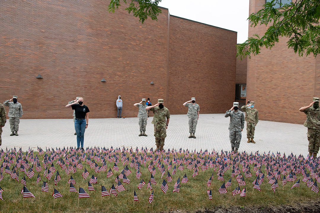 ROTC cadets saluting in front of a field of small American flags.