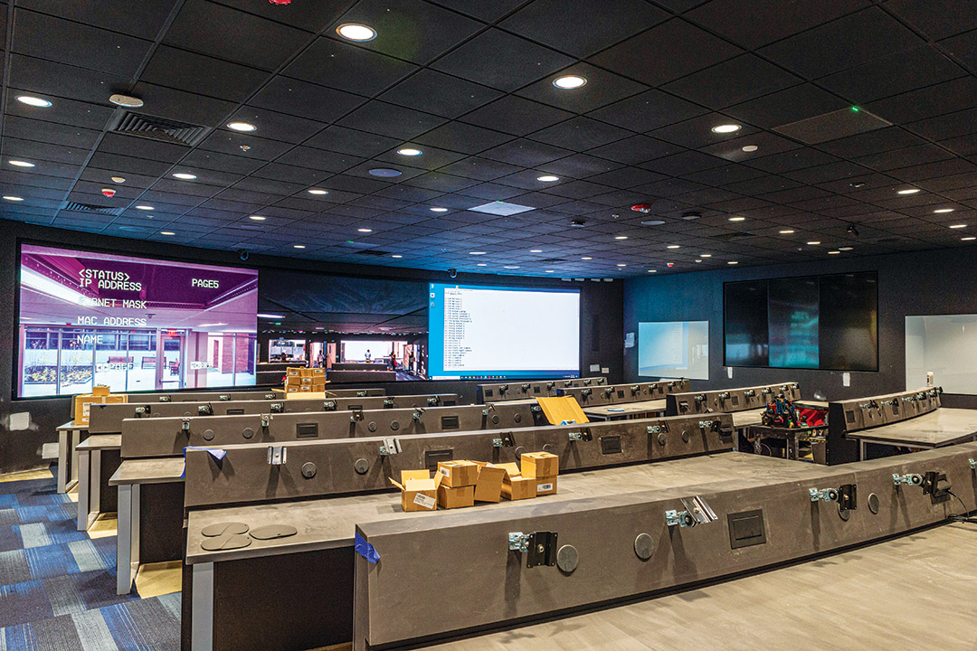 large room with long desks and large TV screens.