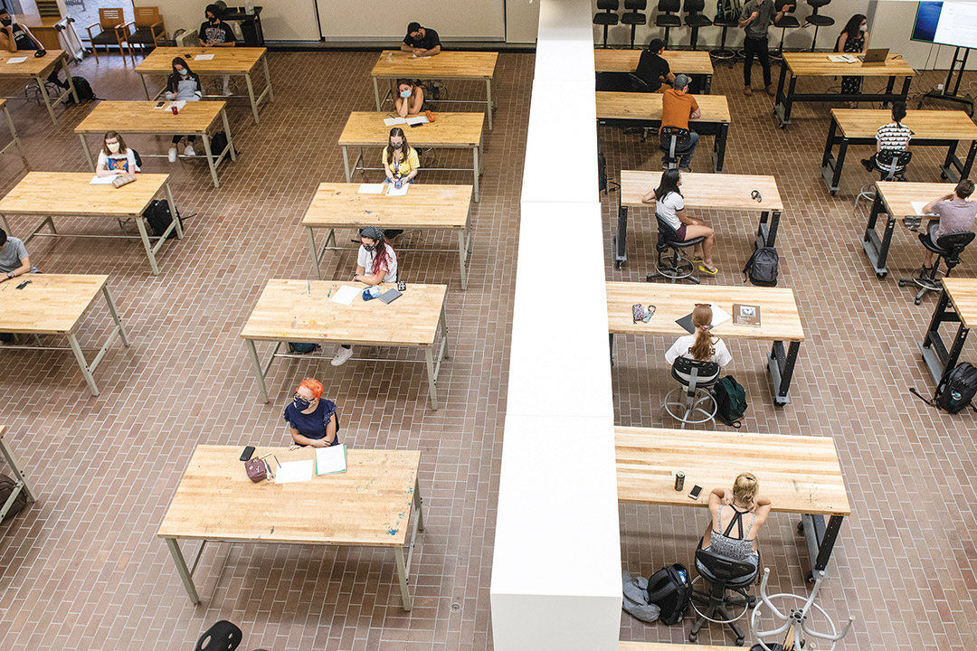 overhead view of students sitting at individual tables.