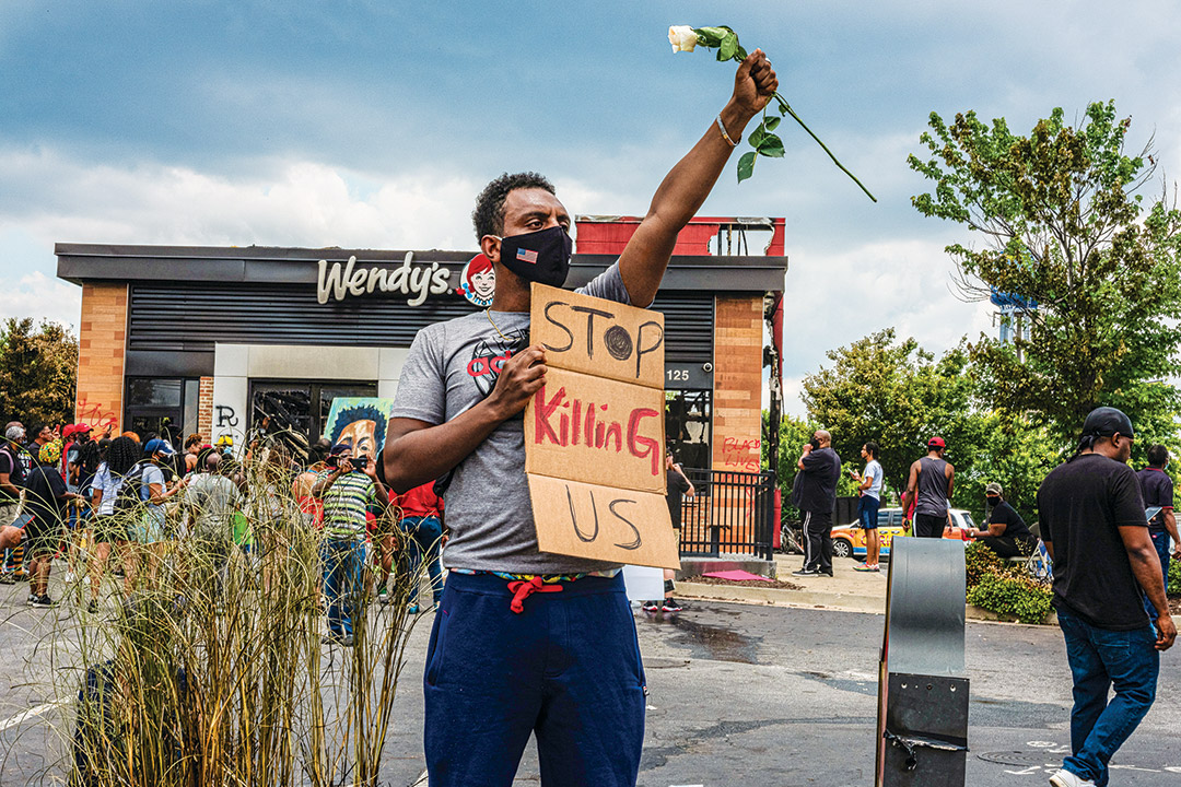 """man holding a white rose and a sign that reads """"stop killing us."""""""