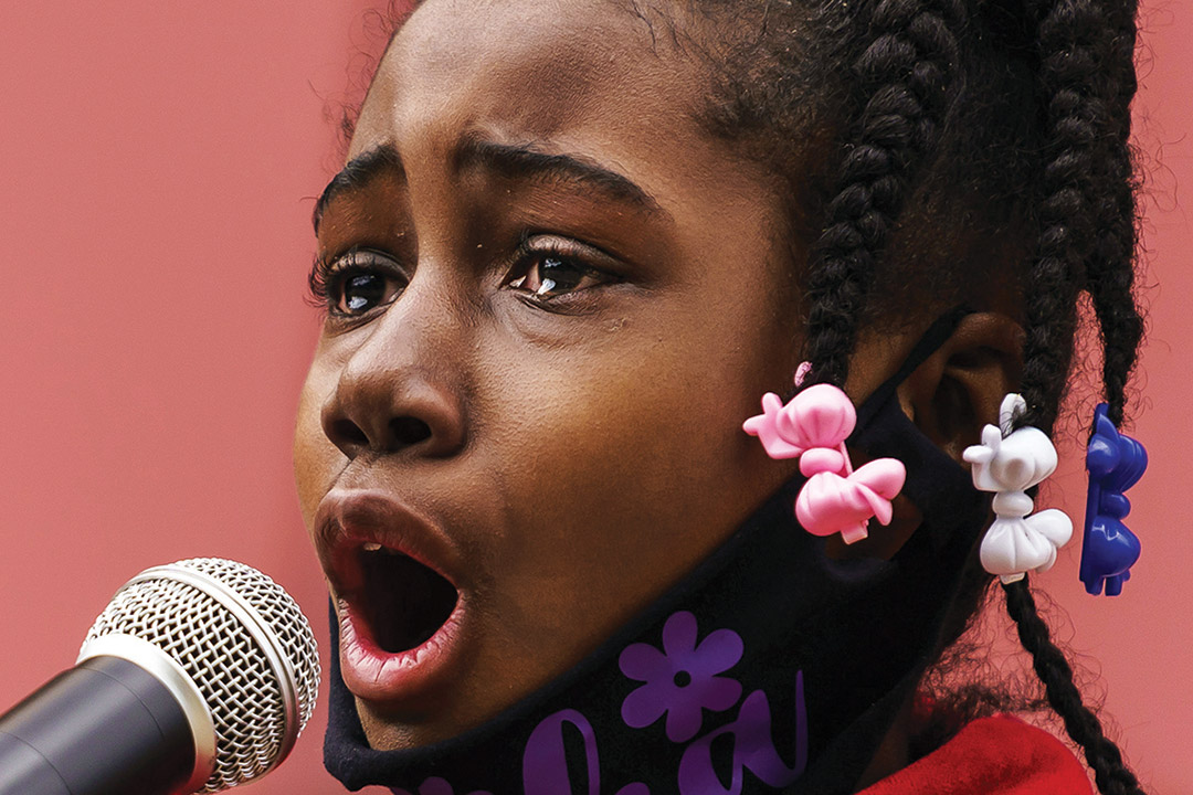 close-up of Black girl speaking into a microphone with tears in her eyes.
