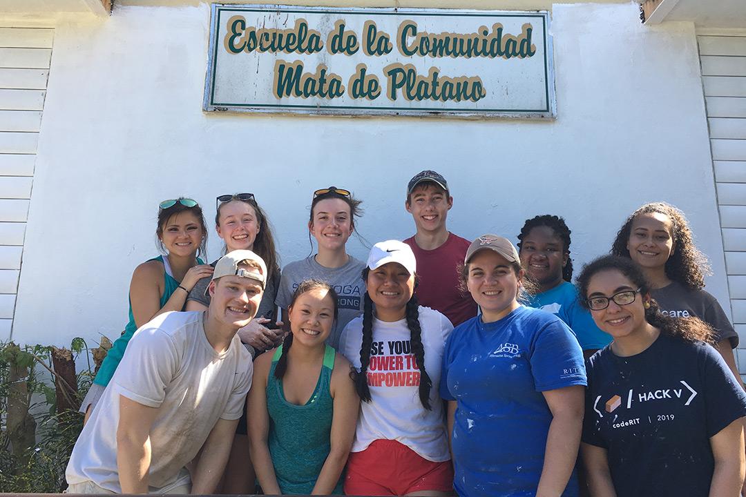 Group of students stands outside building with sign that reads: Escuela de la Comunidad Mata de Platana