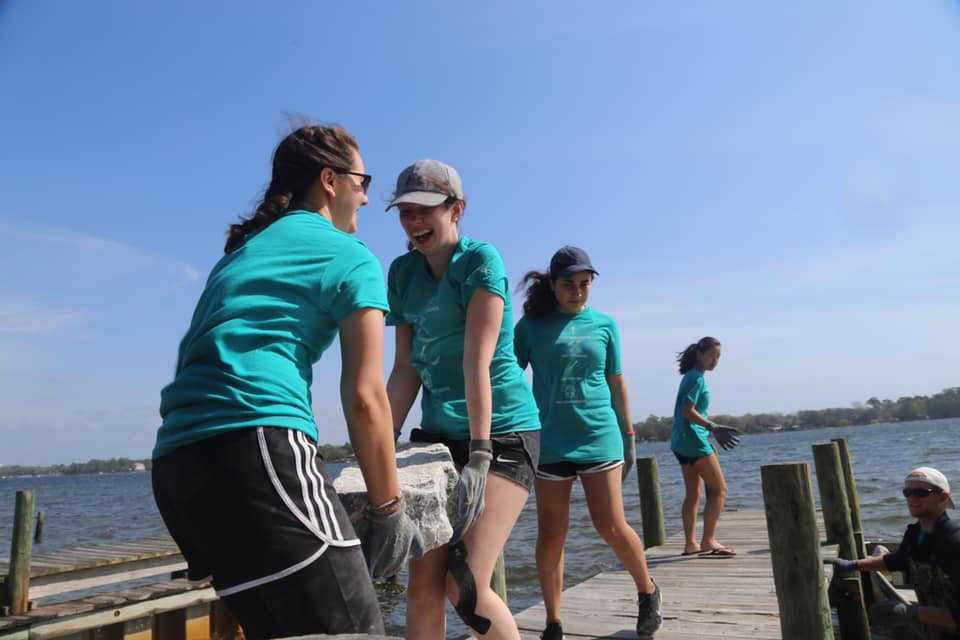 Students carry large rocks down a pier.