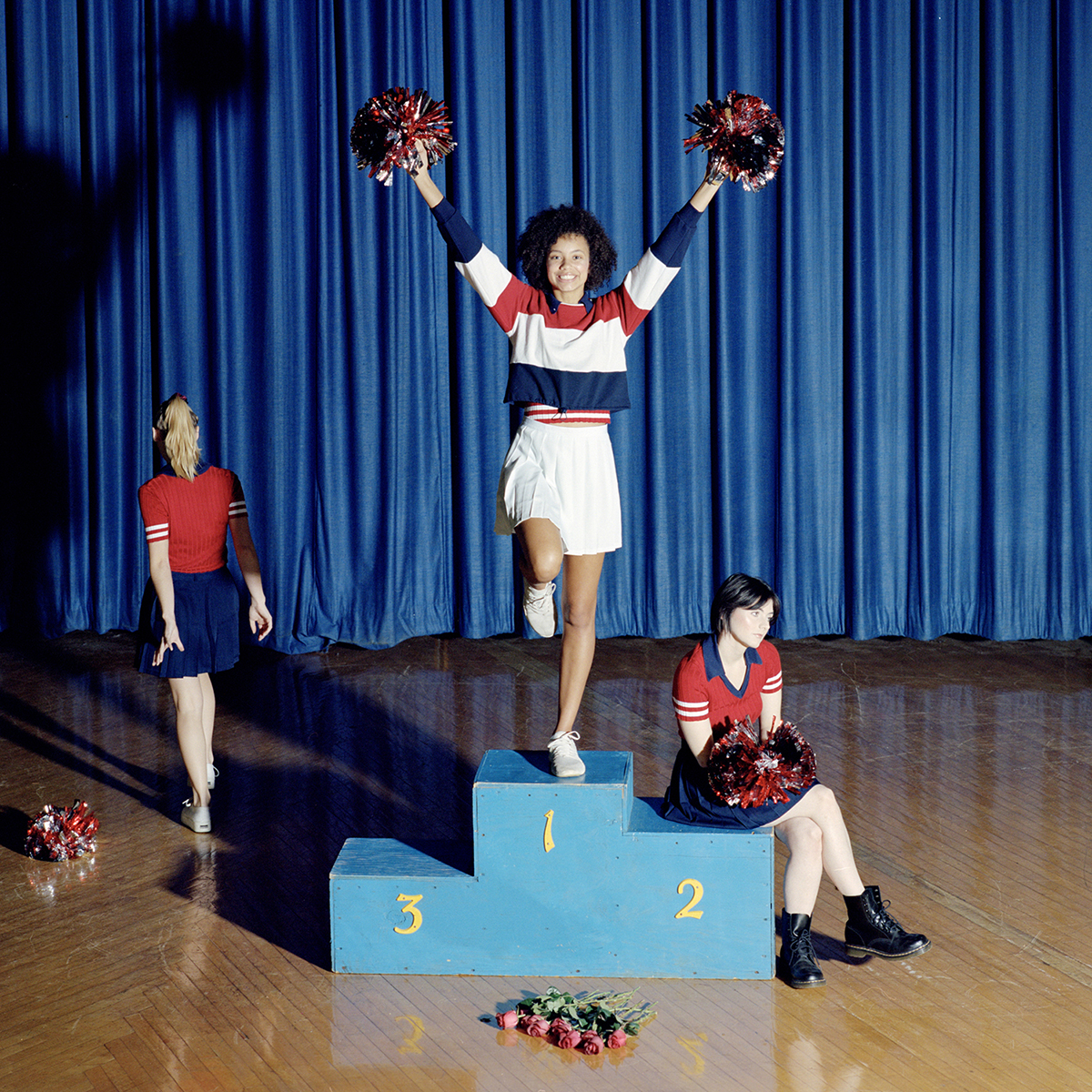 Portrait photography of a cheerleader standing on a podium while another cheerleader walks away and one sits on a podium.
