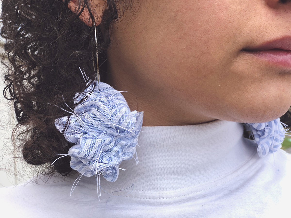 Cloth earrings dangle from a person's ears.