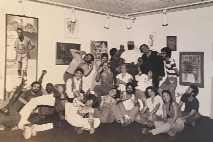 A group of people post in a photo taken in the 1970s.