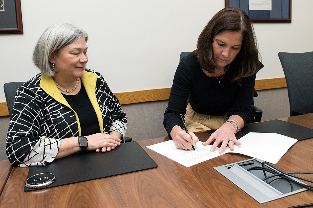 Two women sit at a table, signing documents