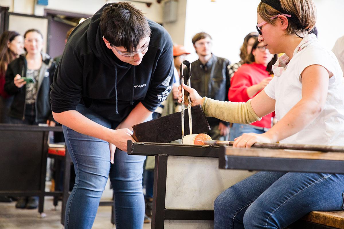 MFA Glass student Kayla Cantu assists Aya Oki with a hot glass demo.