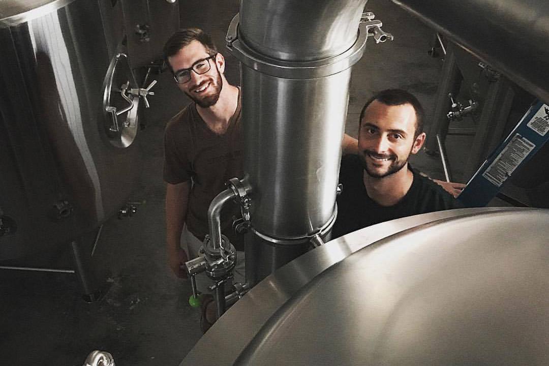 two people standing near vat of beer.