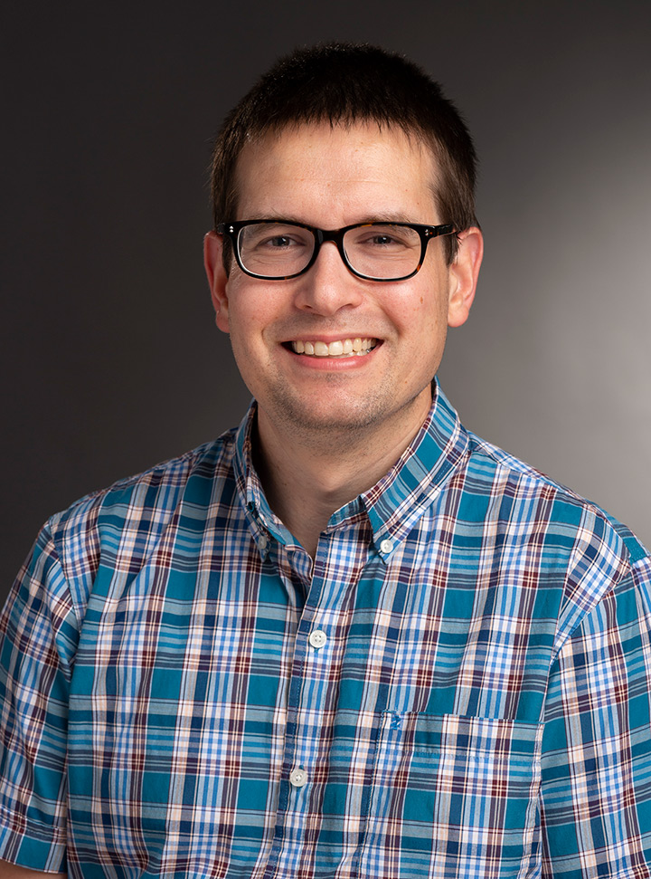 Head-and-shoulders view of man wearing glasses and plaid shirt.