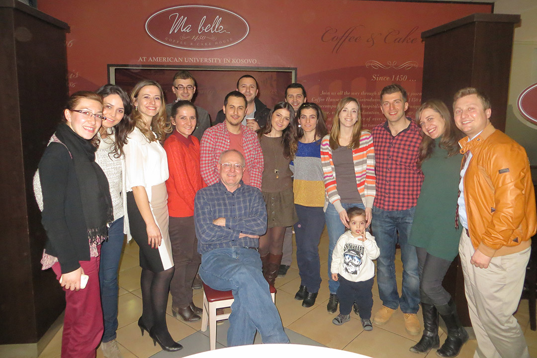 professor posing for photo with students in a restaurant.