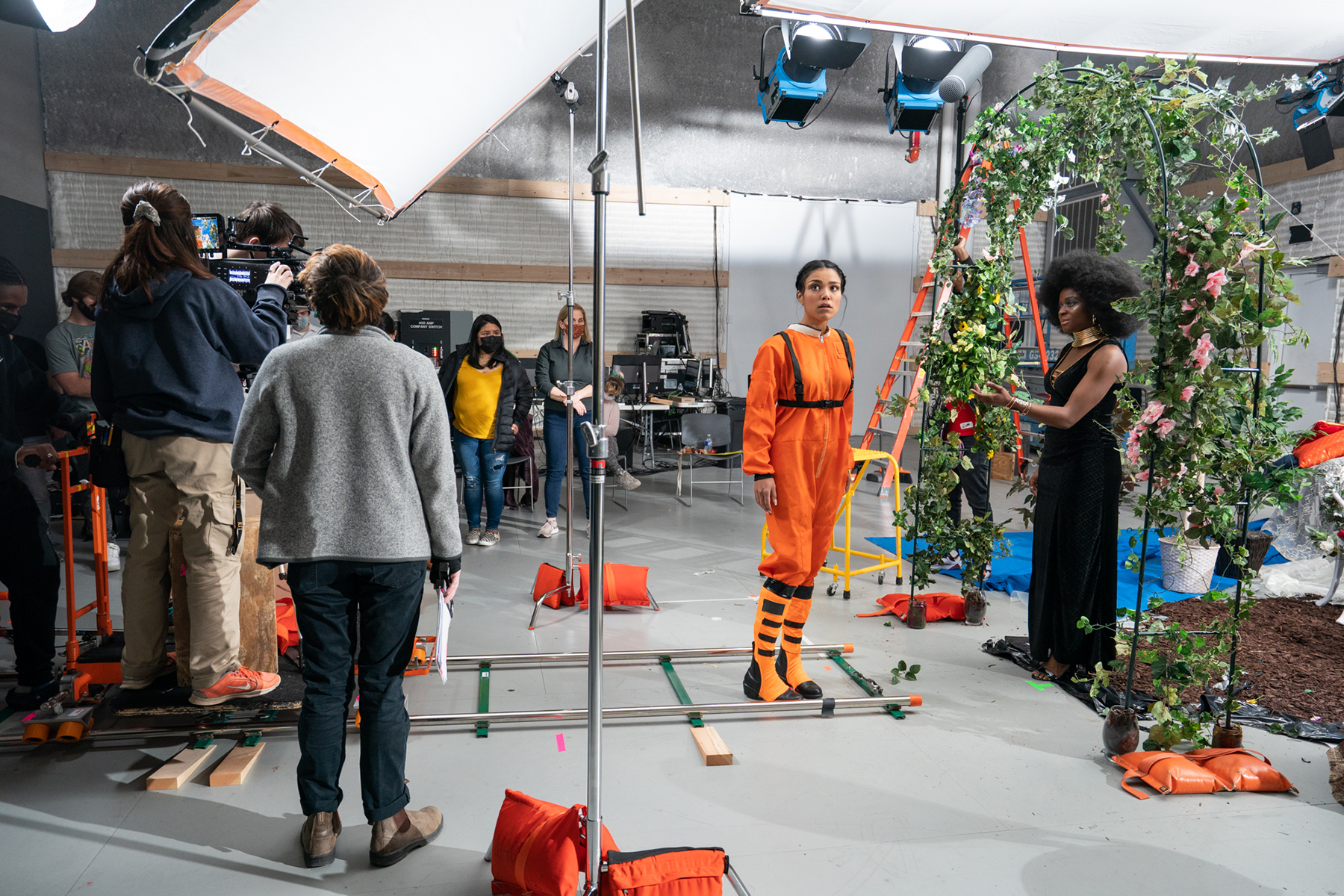 A film crew focuses on an actor in a space suit.