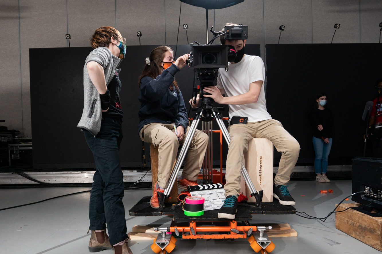 Two students and an alumnus operate a camera together.