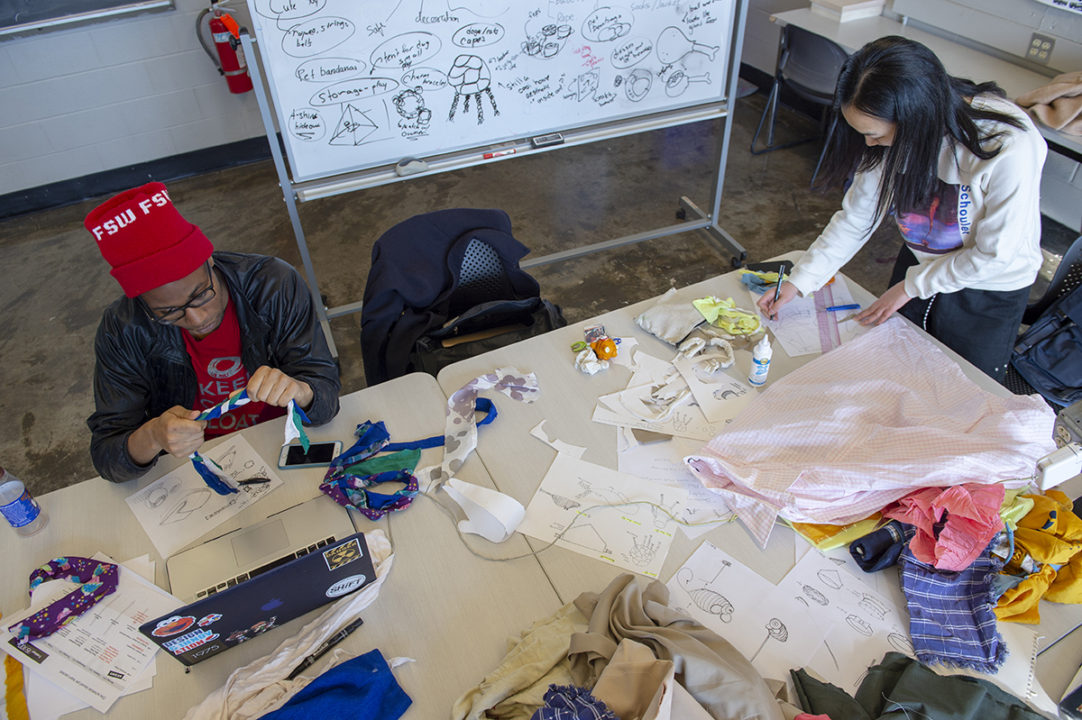 Two students at a table sketching and using fabric to make a product.