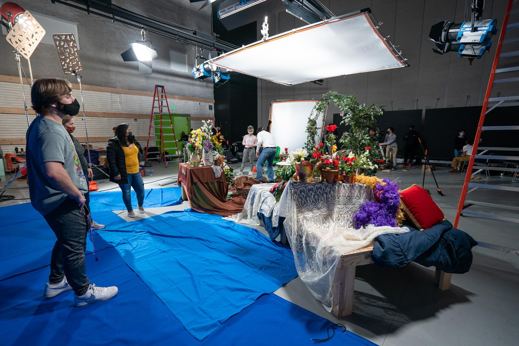 A student film crew surveys the set props.