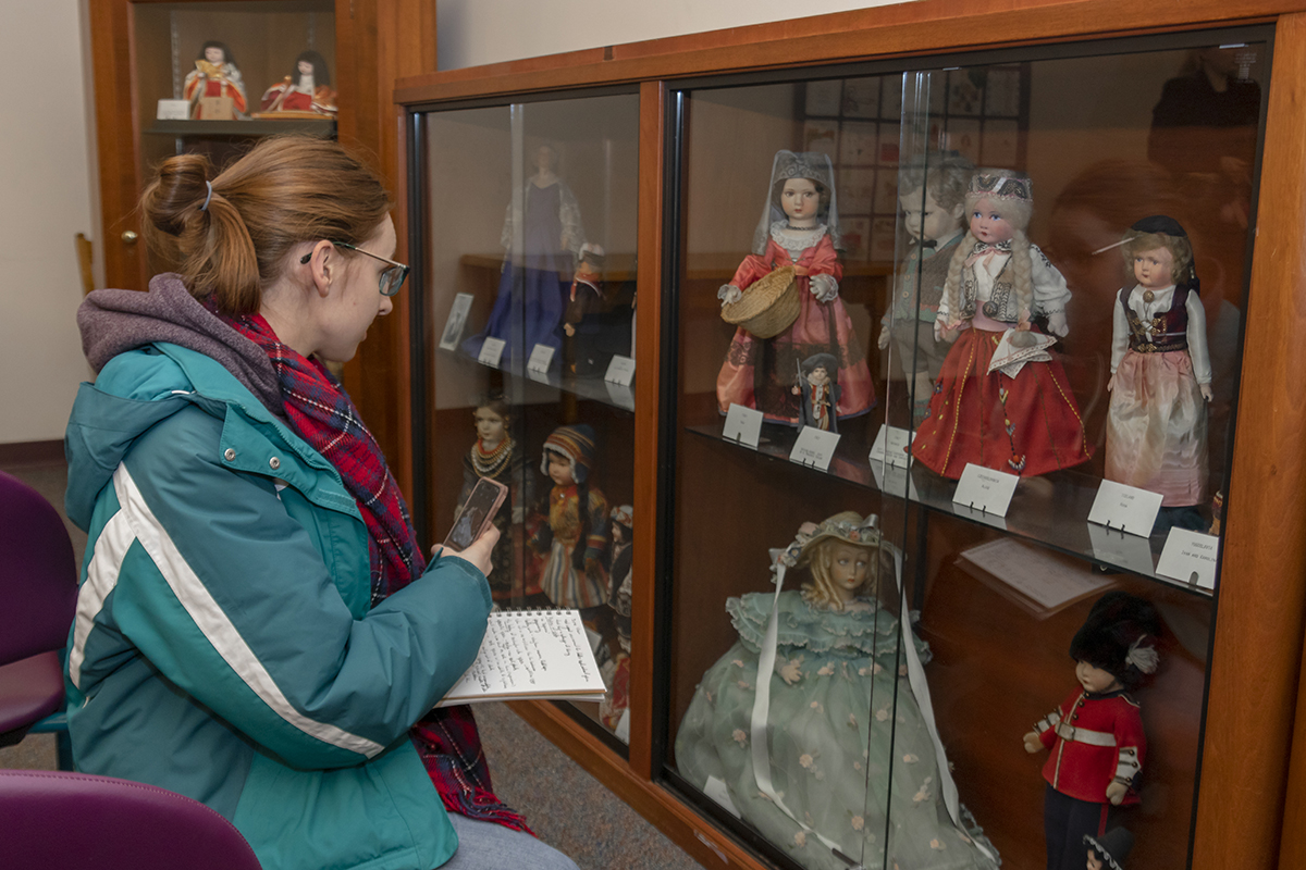 A student observes the doll collection held in the Central Library of Rochester and Monroe County's Secret Room.