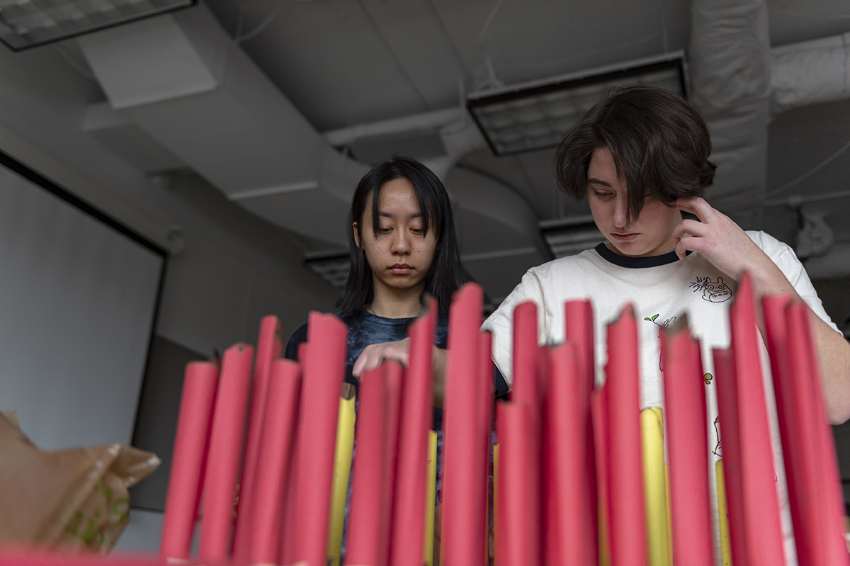 Two students place rolled-up book pages on a grid of pegs.