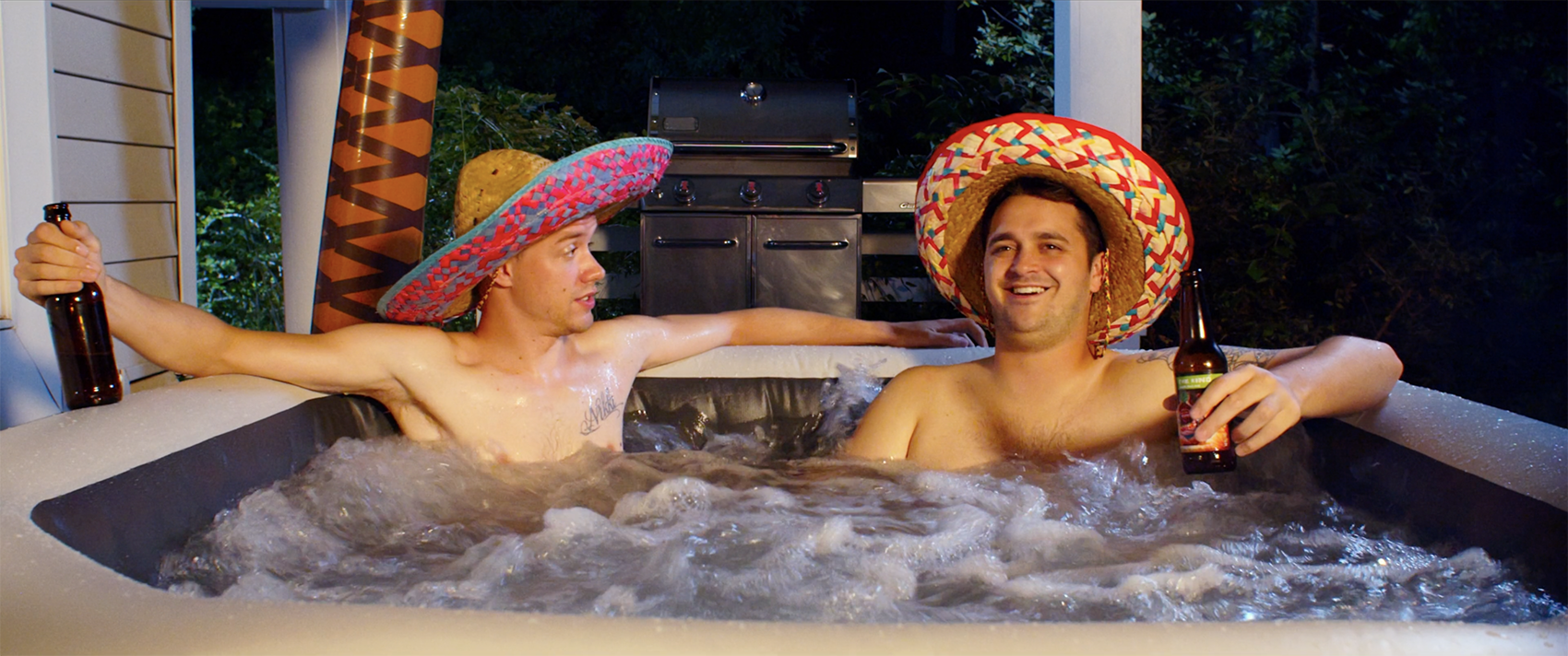 Two guys wearing sombreros sit in a hot tub.