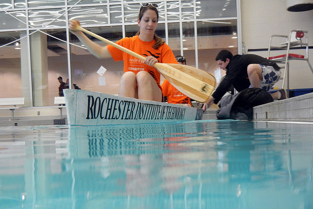 Student floats in concrete canoe in pool.