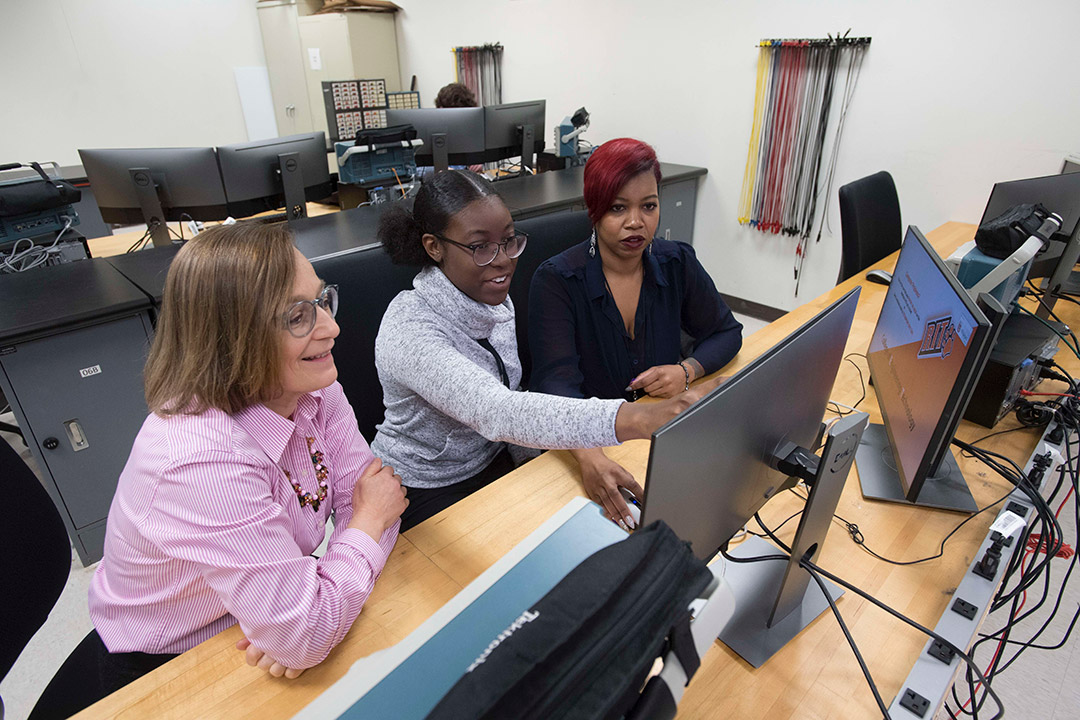 Professor working with two students on computer.