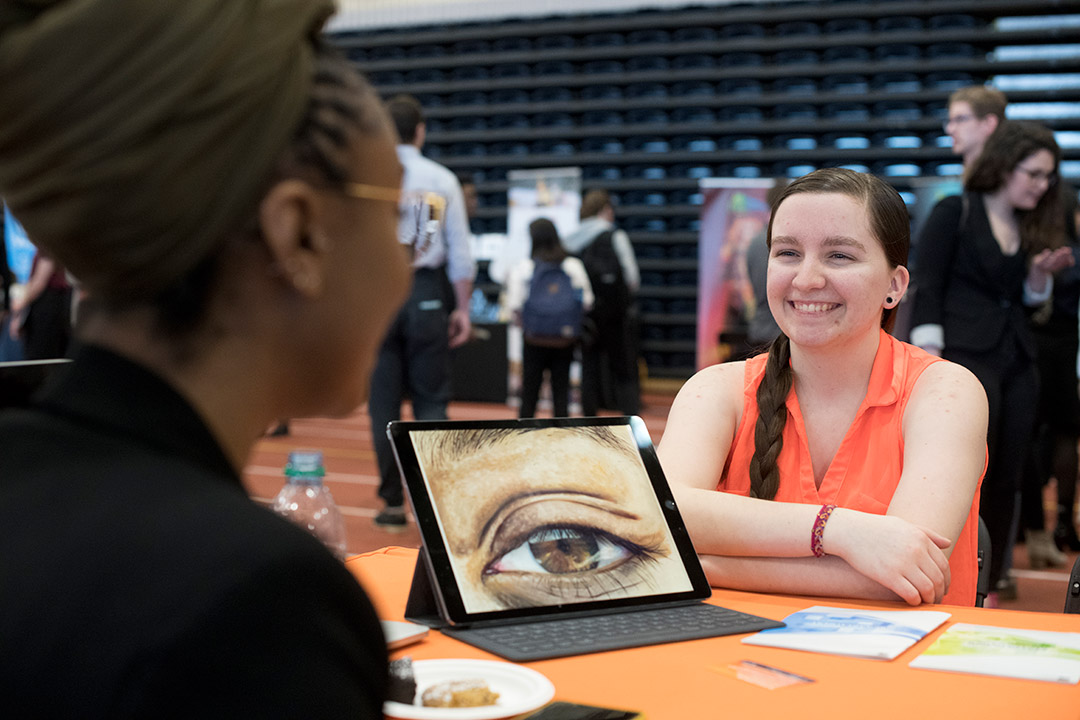 student smiling as she shows graphic illustration of an eye to a company rep.