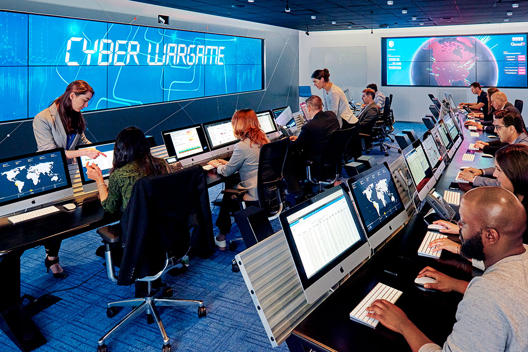 People sit at rows of computers in cyber range.