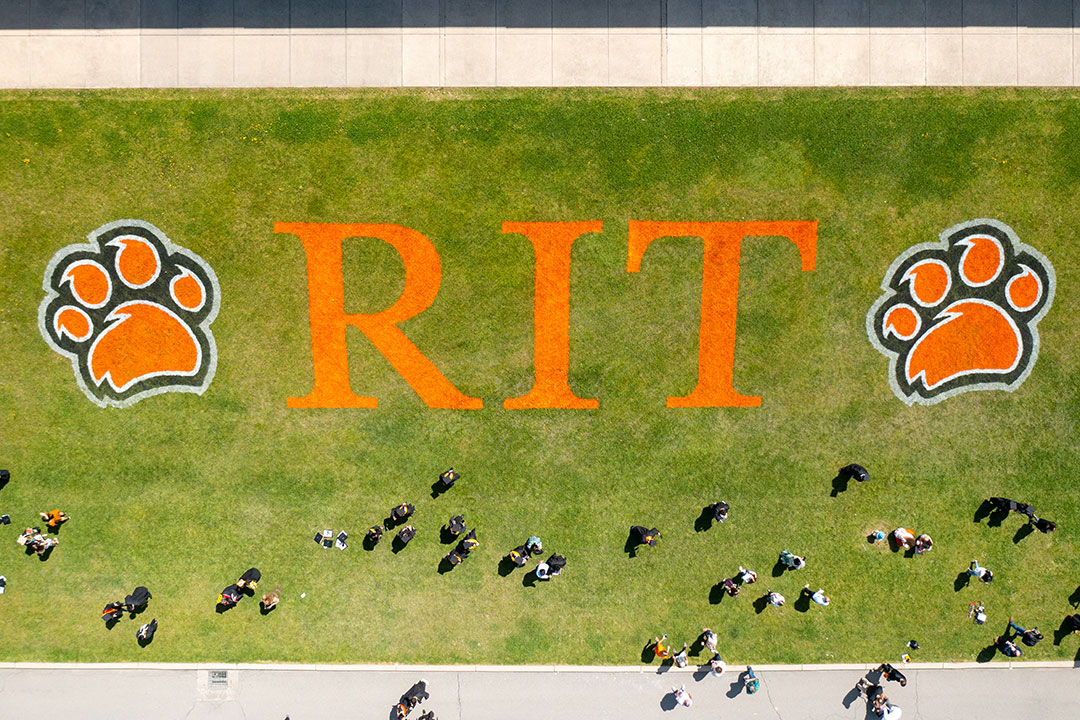 overhead view of students walking on field spray painted with the RIT logo.